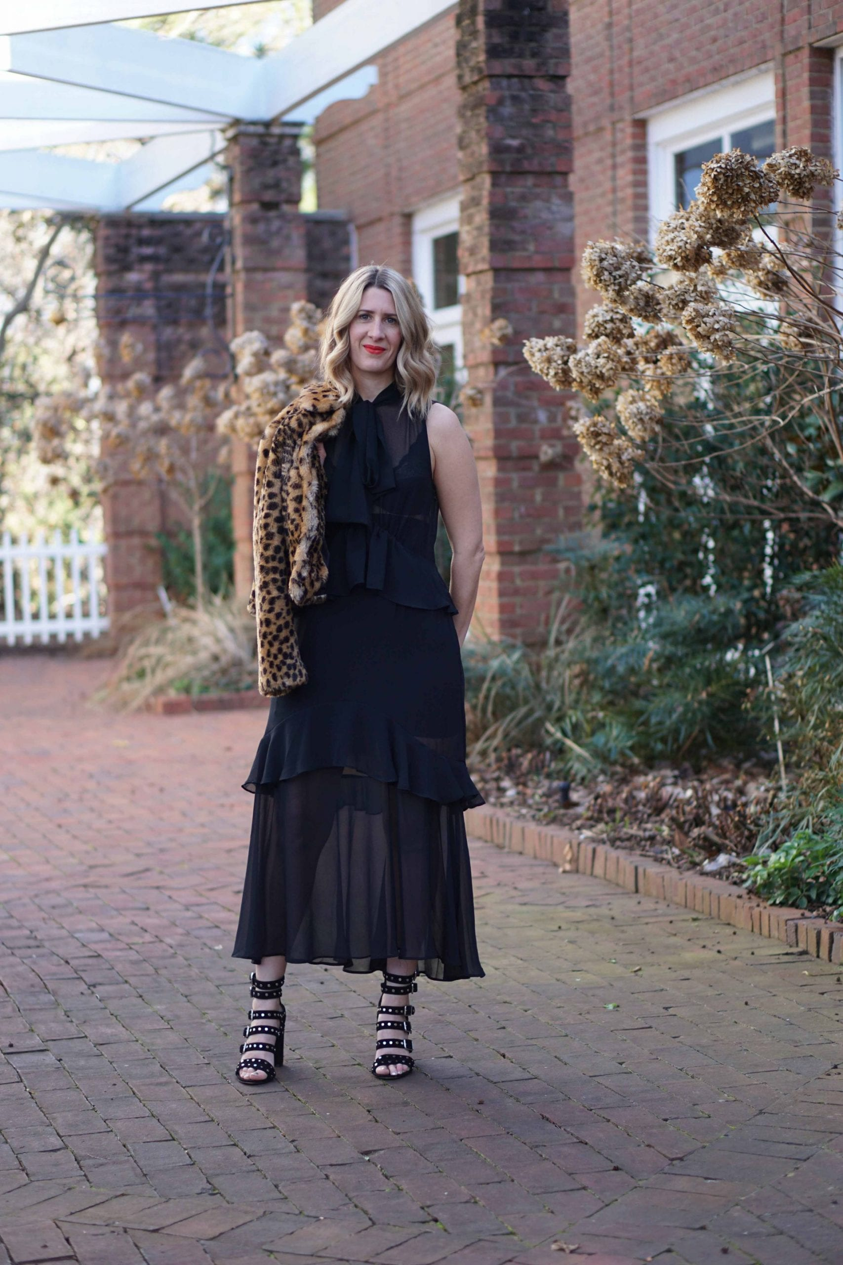 A black sheer dress worn for the evening with a leopard print coat